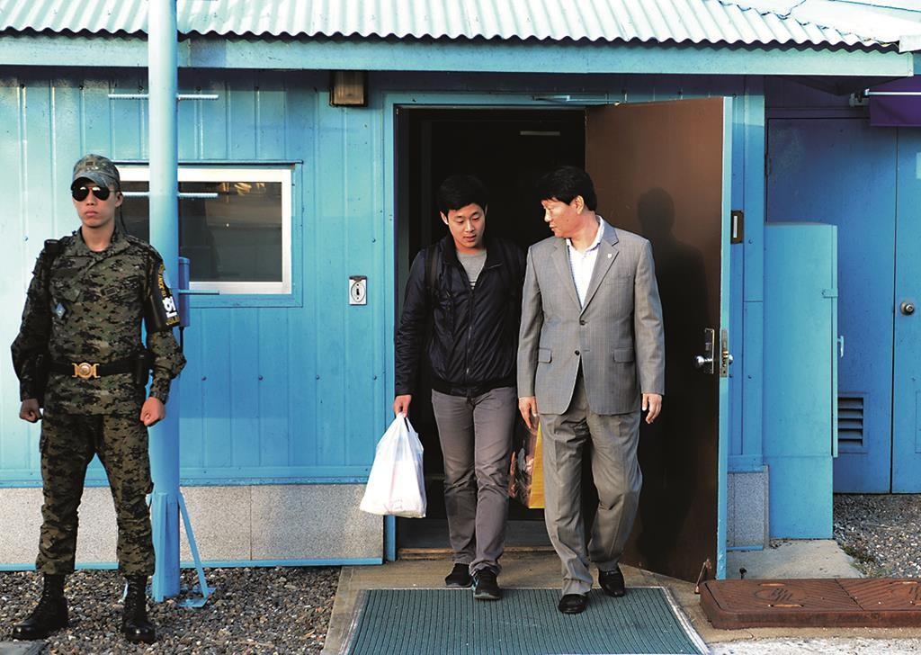 Won Moon Joo, center, a permanent resident of the United States, is escorted Monday by a South Korean official at the border village of Panmunjom, South Korea. (The South Korean Unification Ministry via AP)
