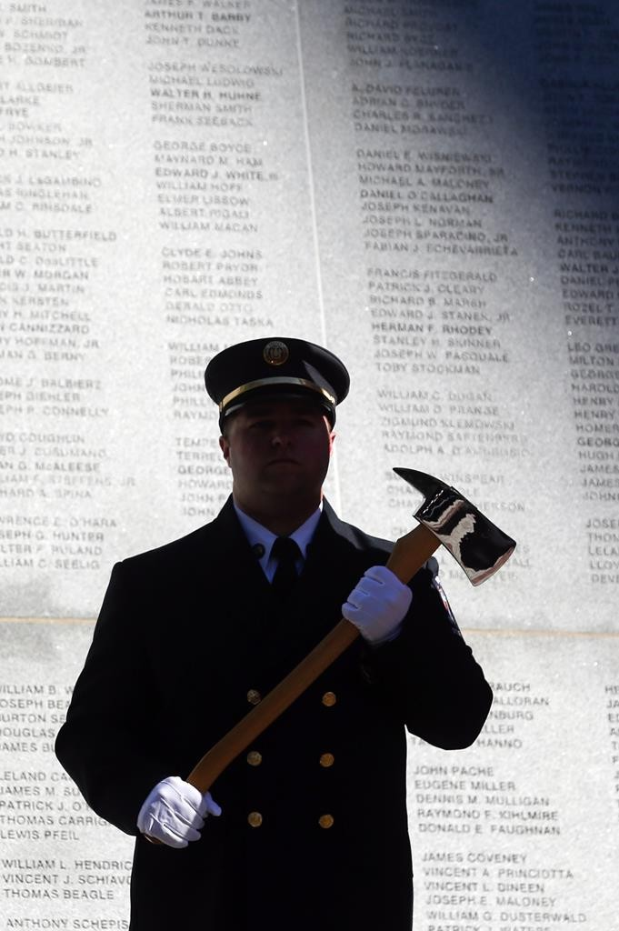 Albany firefighter Jeremy Rue holds an ax during a ceremony at the Fallen Firefighters Memorial in Albany. (AP Photo/Mike Groll)