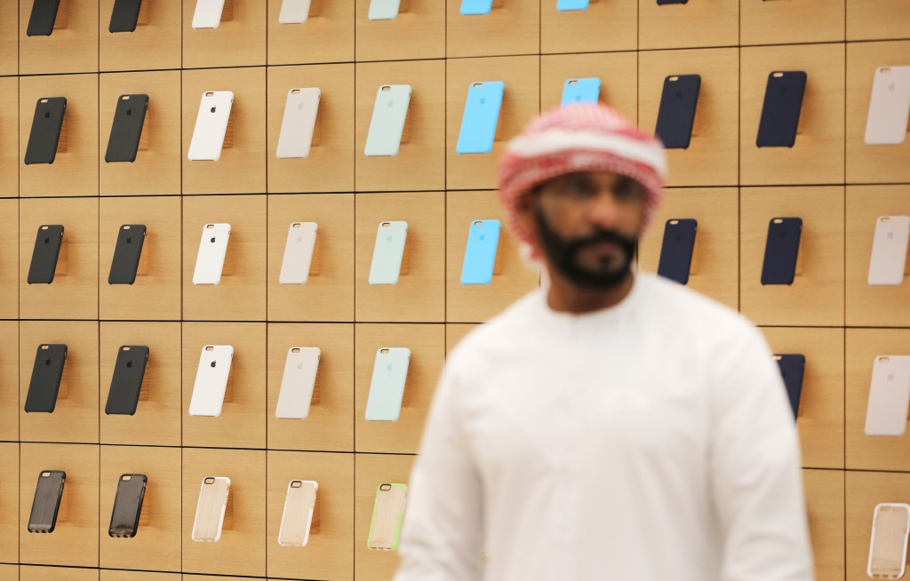 A journalist checks out the latest products at the Apple Store in Dubai. (AP Photo/Kamran Jebreili)