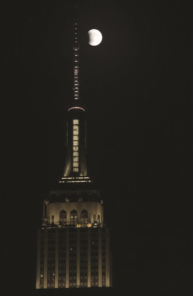A supermoon appears on the right of the Empire State Building in New York Sunday night as a total lunar eclipse occurs. (TelescopeFeed/Flickr)
