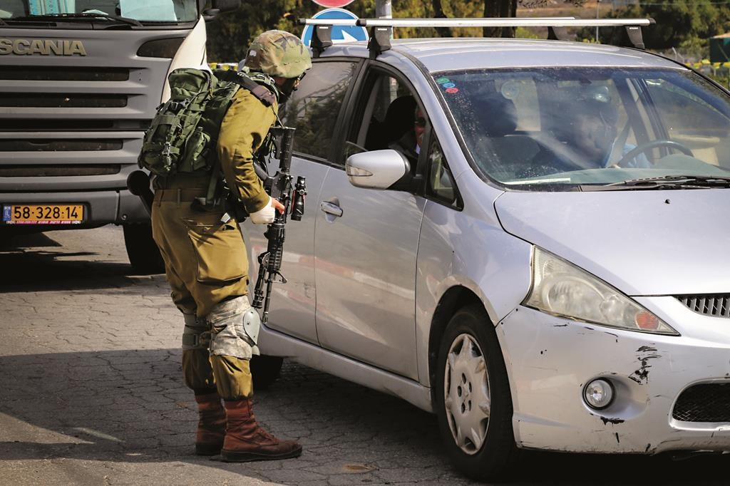 An Israeli soldier checking the IDs of Palestinians near the Gush Etzion junction, the scene of a number of terrorist attacks in recent days. (Gershon Elinson/FLASH90)