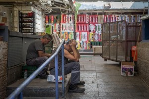 Workers sitting in an alleyway at a deserted Mahane Yehuda Market in Yerushalayim on Thursday, as the wave of terror keeps shoppers away. (Nati Shohat/Flash90)