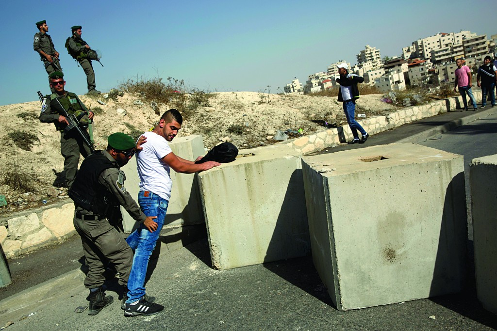 Israeli border police conduct a search next to newly placed concrete blocks in a neighborhood in the eastern part of Yerushalayim. (AP Photo/Oded Balilty, File)