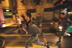 Israeli policemen running in search of a stabbing suspect in Yerushalayim, Wednesday. An Israeli woman was stabbed by an Arab attacker who was then shot, the police spokesman said. (AP Photo/Dusan Vranic)