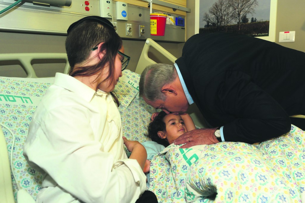 """Prime Minister Binyamin Netanyahuvisits the lightly injured son of Rabbi Aharon Banita, Hy""""d, who was murdered in the stabbing attack in the Old City of Yerushalayim. His wife, Adele, was seriously wounded in that attack. (Kobi Gideon/GPO)"""