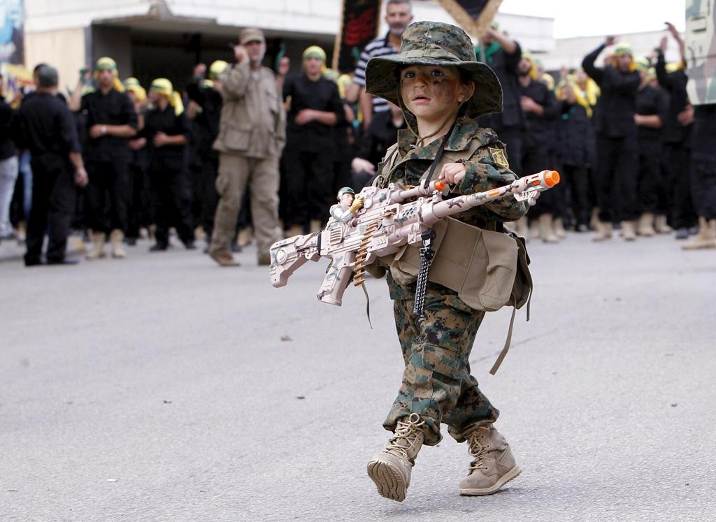 A boy in Hizbullah uniform carrying a toy gun walks during the funeral of three Hizbullah terrorists who were killed while fighting alongside Syrian army forces in Syria in Nabatieh town, southern Lebanon, Tuesday. (REUTERS/Ali Hashisho)