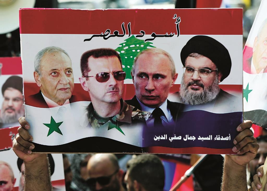 """A Syrian who lives in Lebanon holds a poster with photos of (L-R:) Lebanese Parliament Speaker Nabih Berri, Syrian President Bashar Assad, Russian President Vladimir Putin, Hizbullah leader Sheikh Hassan Nasrallah, with Arabic that reads """"Lions of the time,"""" during a rally to thank Moscow for its intervention in Syria, in front of the Russian embassy in Beirut, Sunday, Oct. 18, 2015.  (AP Photo/Bilal Hussein)"""