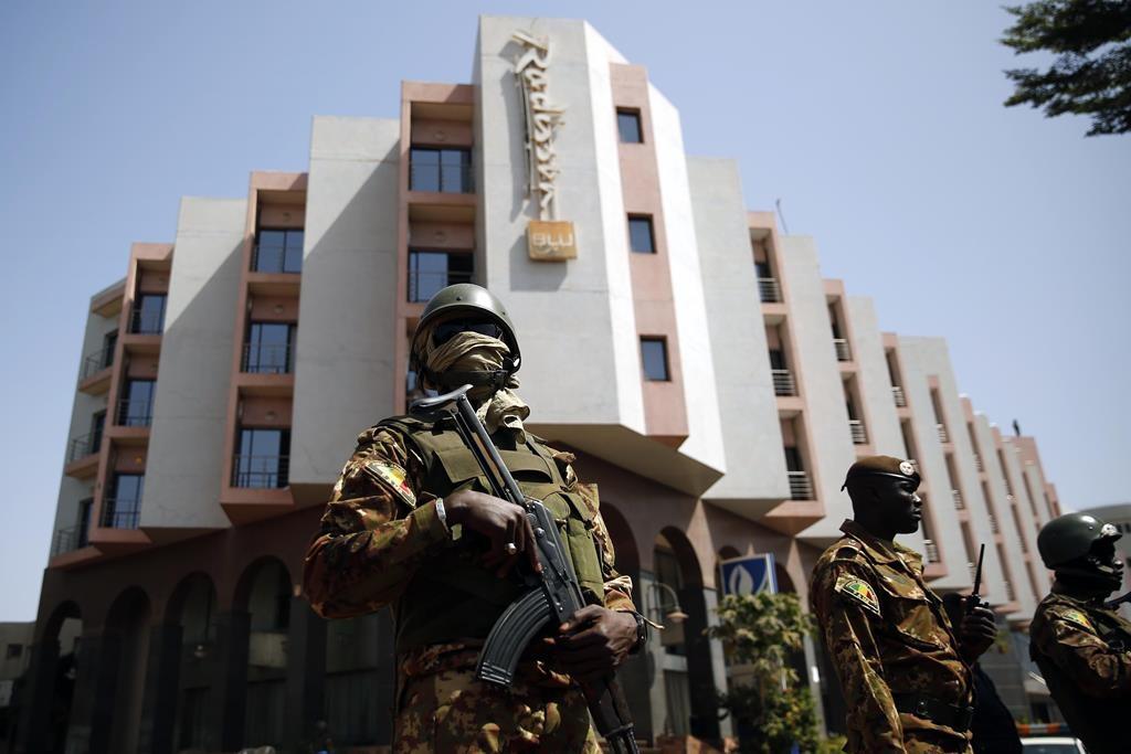 Tight security surrounds Malian President Ibrahim Boubacar Keita as he visits the Radisson Blu hotel in Bamako, Mali, Saturday.  (AP Photo/Jerome Delay)