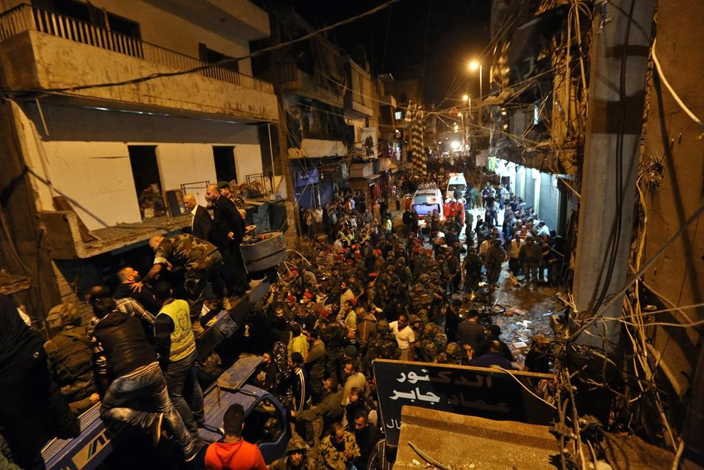 Lebanese army and civilians gather near the site of a twin suicide attack in Burj al-Barajneh on Thursday. (AP Photo/Bilal Hussein)