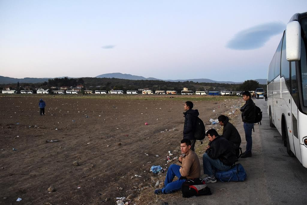 Migrants and refugees sit outside of a bus as they wait to pass from the northern Greek village of Idomeni to southern Macedonia, Monday.  (AP Photo/Giannis Papanikos)