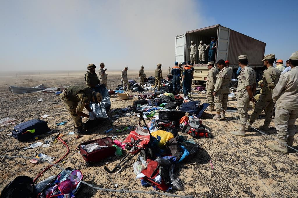 In this Russian Emergency Situations Ministry photo made available on Monday, Egyptian soldiers collect personal belongings of victims at the crash site of a passenger plane bound for St. Petersburg, Russia, in Hassana, Egypt's Sinai Peninsula, on Monday.  (Russian Ministry for Emergency Situations photo via AP)