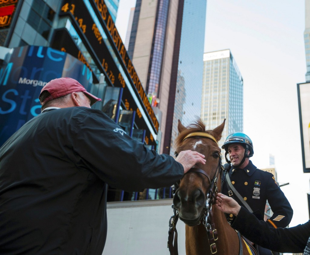 Pedestrians pet the horse of a New York Police Department officer as he stands in the Times Square district of New York during an increase in security following fatal explosions in Boston, in this file photo.  (REUTERS/Lucas Jackson/Files)