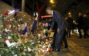 French President Francois Hollande and U.S. President Barack Obama place flowers at a makeshift memorial to pay tribute to the victims of the Paris attacks at the Bataclan in Paris, late Sunday. (REUTERS/Kevin Lamarque)
