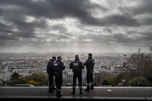 Paris is seen in the background as French police officers stand on guard near a church, on top of the Montmartre hill, in Paris, Wednesday.  (AP Photo/Daniel Ochoa de Olza)
