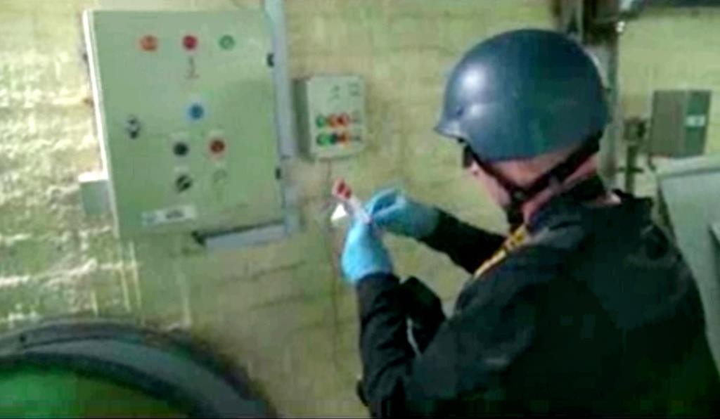 This image made from video broadcast on Syrian media on Oct. 8, 2013, purports to show a chemical weapons expert taking samples at a chemical weapons plant at an unknown location in Syria. (Syrian State Media via AP video, File)