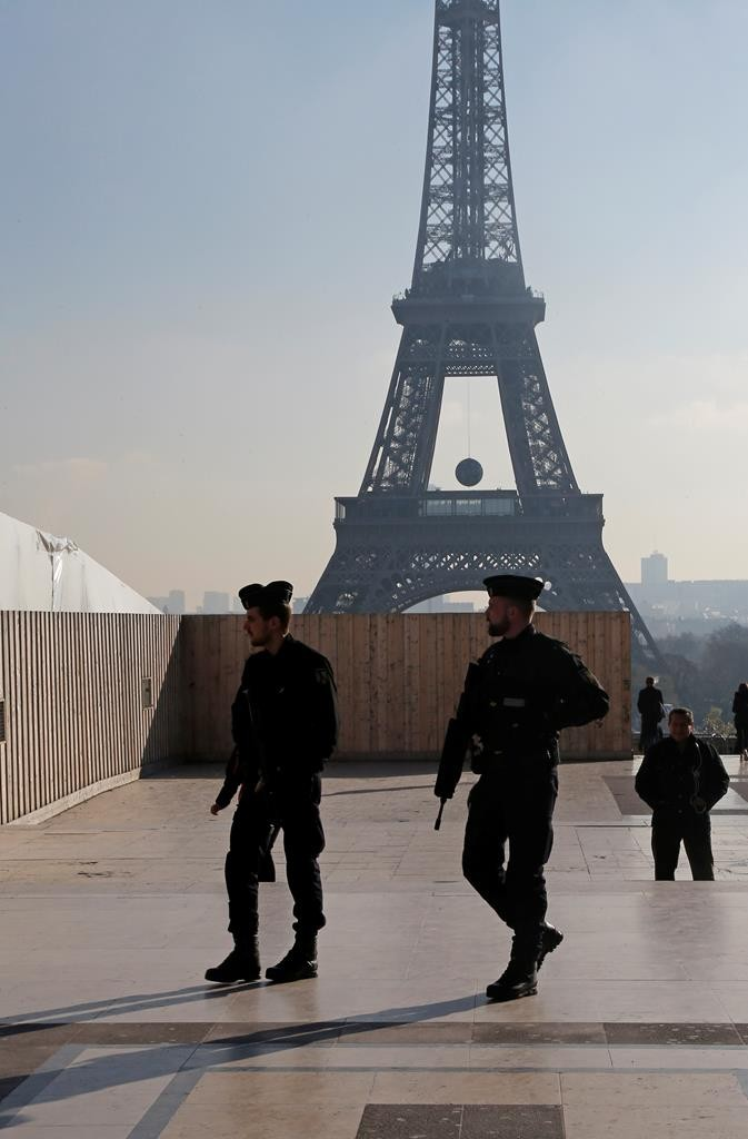 French police officers patrol near the Eiffel Tower, in Paris, on Monday.  (AP Photo/Jacques Brinon)