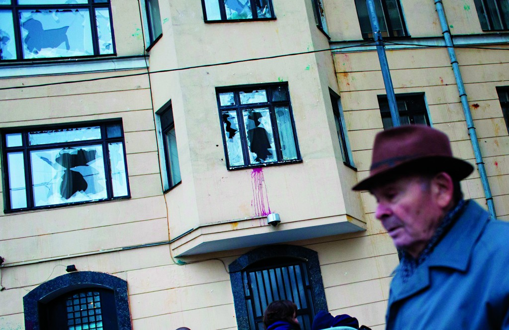 An elderly man walks past the Turkish Embassy with broken window planes in Moscow, Russia, on Wednesday. Windows at the embassy's compound were shattered on the first and second floors and eggs pelted against the walls on Wednesday after a protest there went sour.  (AP Photo/Ivan Sekretarev)