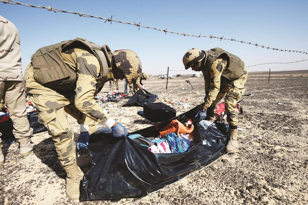 Egyptian soldiers collect personal belongings of plane crash victims at the crash site of a passenger plane bound for St. Petersburg in Russia that crashed in the Hassana area in Egypt's Sinai Peninsula.  (Russian Ministry for Emergency Situations photo via AP)