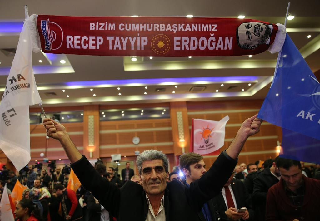 """A supporter of Turkey's President Recep Tayyip Erdogan and The Justice and Development Party, (AKP), holds up a Turkish banner that reads: """"Our President is Recep Tayyip Erdogan,"""" as he celebrates at the AKP headquarters, in Istanbul, Sunday. (AP Photo/Hussein Malla)"""