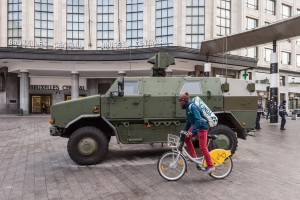 A man cycles by a Belgian Army vehicle parked in front of the main train station in the center of Brussels on Sunday. (AP Photo/Geert Vanden Wijngaert)