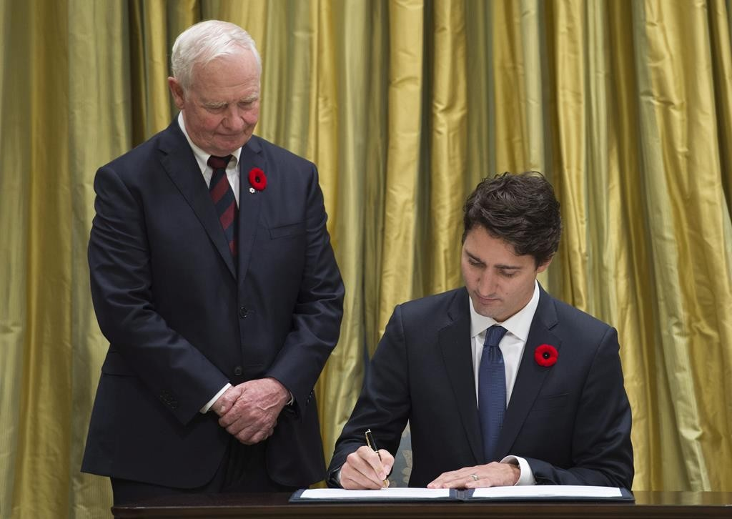Governor General David Johnston watches as Prime Minister Justin Trudeau signs papers to become prime minister during a ceremony Wednesday in Ottawa.  (Adrian Wyld/The Canadian Press via AP)