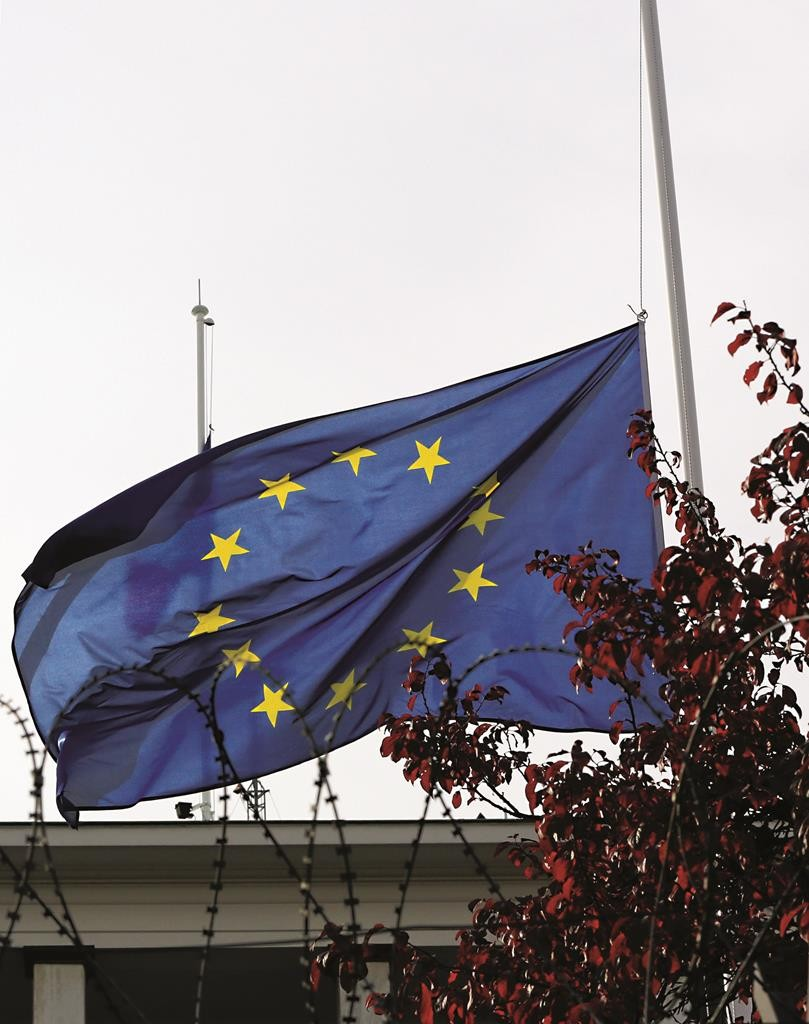 A French and a European Union flag are lowered at half staff over the French embassy in Ankara, Turkey, Monday, Nov. 16. (AP Photo/Burhan Ozbilici)