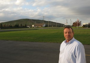 Rich Swinehart, CEO of Waterloo Container, which provides bottles to wineries in the Finger Lakes region, stands outside his business with the Seneca Meadows Landfill in the background. (AP Photo/Mary Esch)