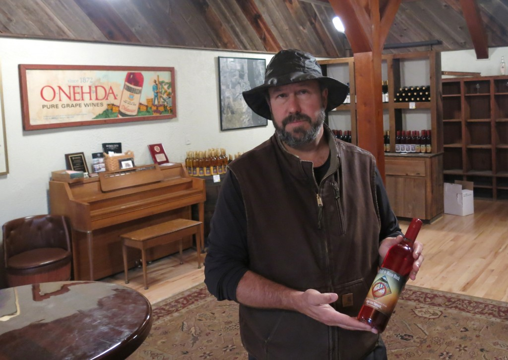 "Will Ouweleen, owner of Eagle Crest and O-Neh-Da wineries, poses with a bottle of ""No Trash! Di Blasio Blush"" in Conesus, N.Y. (AP Photo/Mary Esch)"