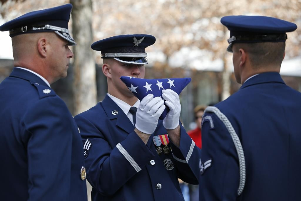 United States Air Force Honor Guard Austin Robedeaux holds a flag Monday during a ceremony at the 9/11 Memorial honoring first responders who were also military veterans. (AP Photo/Kathy Willens)