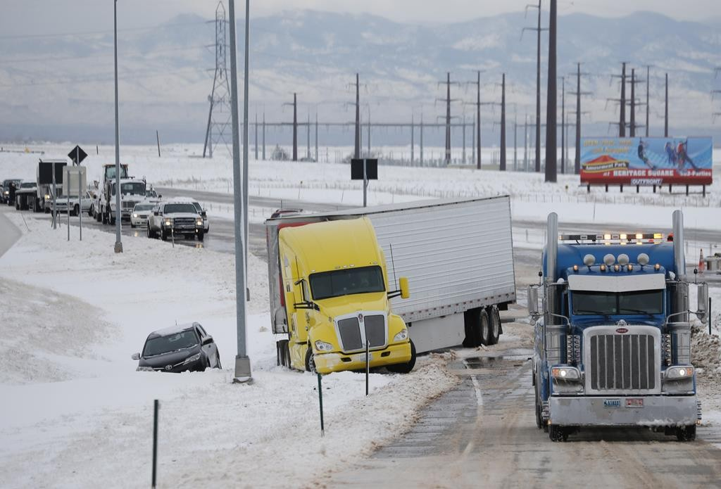 A tow truck, right, pulls up to clear a tractor-trailer and sports utility vehicle stuck in snow on an off-ramp off Interstate 70 as a winter storm packing high winds and snow blankets the plains Tuesday, in Aurora, Colo. (AP Photo/David Zalubowski)