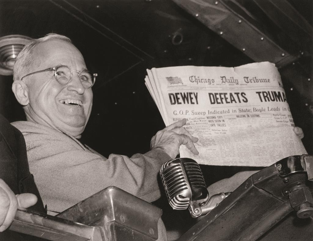 """President Harry S. Truman holds up an Election Day edition of the Chicago Daily Tribune, which, based on early results, mistakenly announced """"Dewey Defeats Truman."""" )AP Photo/Byron Rollins("""