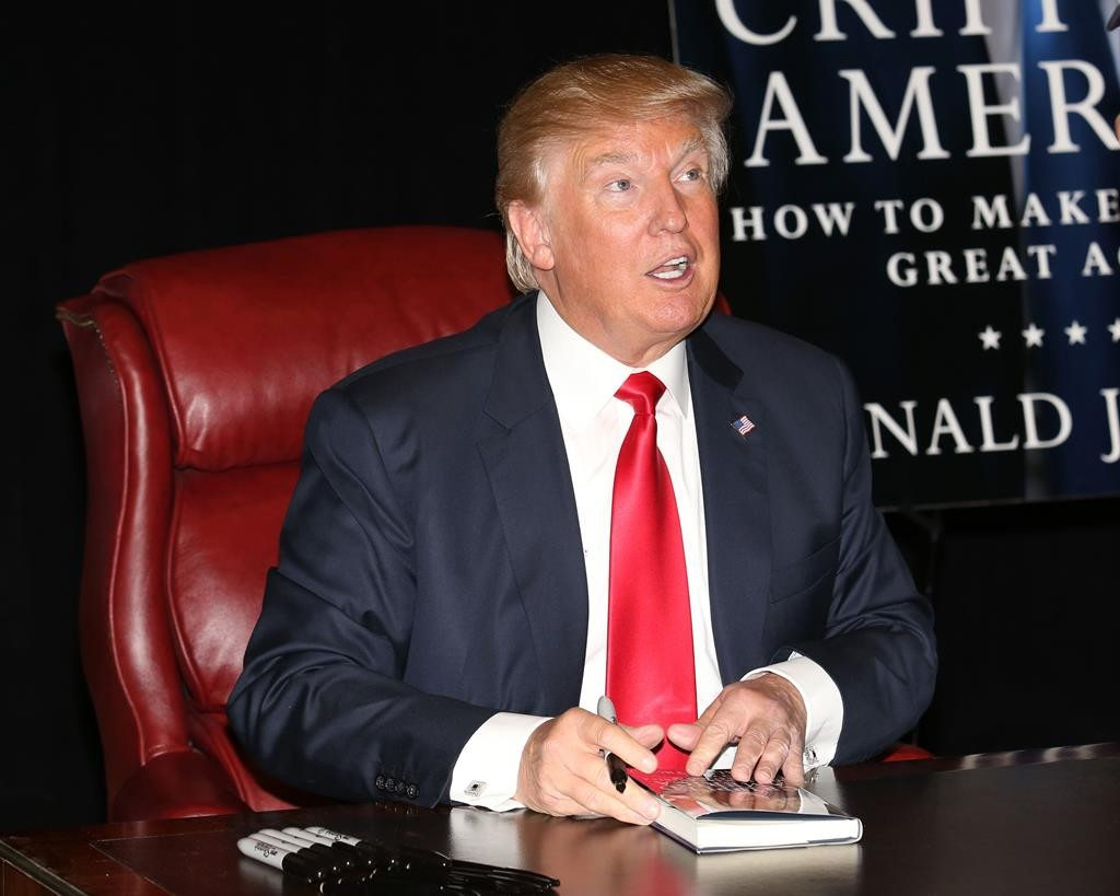 Businessman and Republican presidential candidate Donald Trump signs copies of his new book, at Trump Tower on Tuesday, in New York. (Greg Allen/Invision/AP)