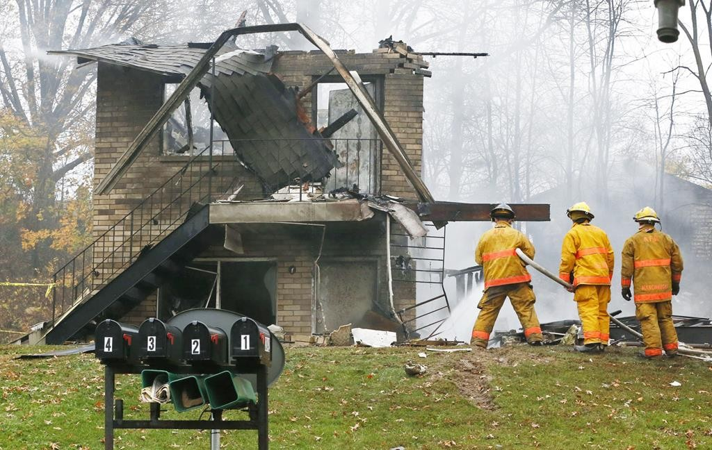 Firefighters work at the scene where authorities say a small business jet crashed into an apartment building in Akron, Ohio, Tuesday. (Ed Suba Jr./Akron Beacon Journal via AP)