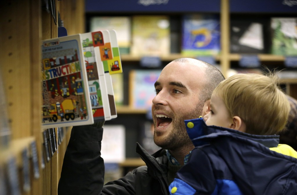 Customer Michael Wallenfels looks at children's books with his two-year-old son at the opening day for Amazon Books in Seattle Tuesday. (AP Photo/Elaine Thompson)