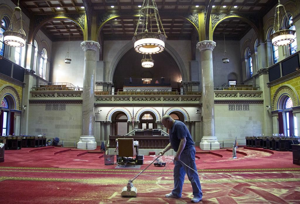 With legislators' desks moved, workers on Monday clean carpets in the Assembly Chamber in preparation for Albany's 2016 legislative session, which begins next month. (AP Photo/Mike Groll)