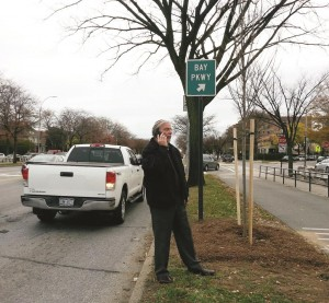 "Assemblyman Dov Hikind on Thursday stands next to the intersection of Ocean Parkway and Bay Parkway under the new sign reading ""Bay Parkway."" (Office of Assemblyman Hikind)"