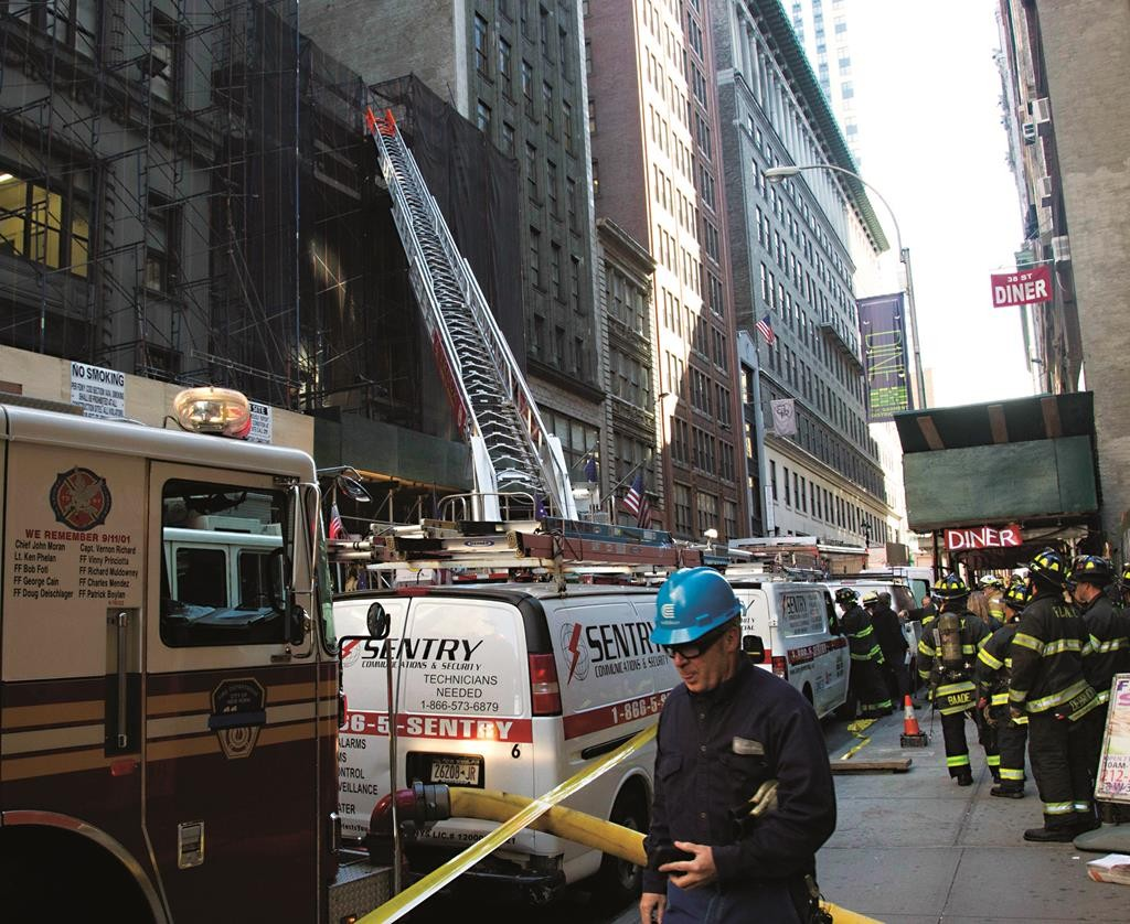 Firefighters gather Friday at the site of a building collapse in Manhattan. (AP Photo/Bebeto Matthews)