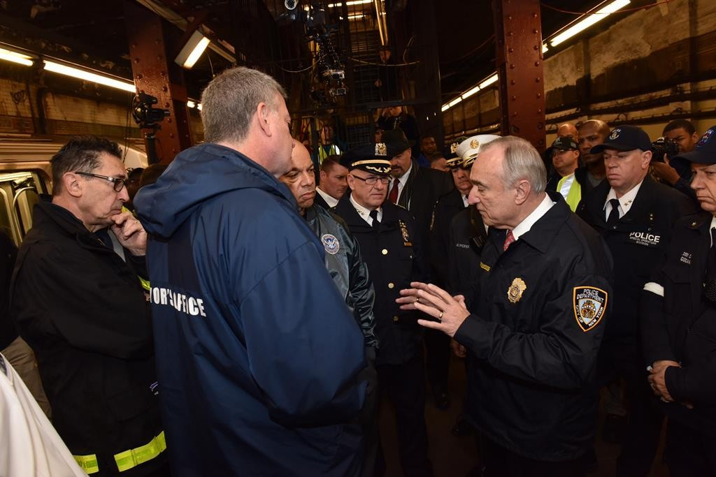 From left, Fire Commissioner Daniel A. Nigro, Mayor Bill de Blasio and Secretary of Homeland Security Jeh C. Johnson, listen Sunday as Police Commissioner William Bratton addresses a news conference following an active shooter drill in an abandoned subway station. (NYPD)