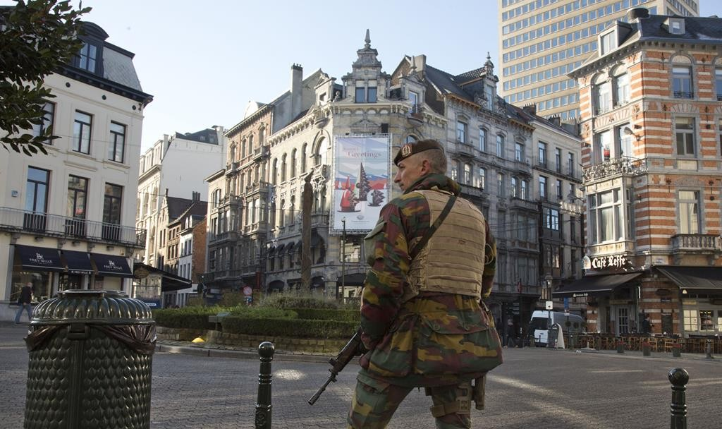 A Belgian Army soldier patrols in the Sablon District of Brussels on Monday. The Belgian capital has entered its third day of lockdown, with schools and underground transport shut and more than 1,000 security personnel deployed across the country. (AP Photo/Virginia Mayo)