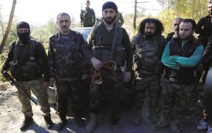 Alpaslan Celik, a deputy commander in a Syrian Turkmen brigade (C), holds handles believed to be parts of a parachute of the downed Russian warplane near the northern Syrian village of Yamadi, near the Turkish-Syrian border, Syria, Tuesday.  (Reuters)