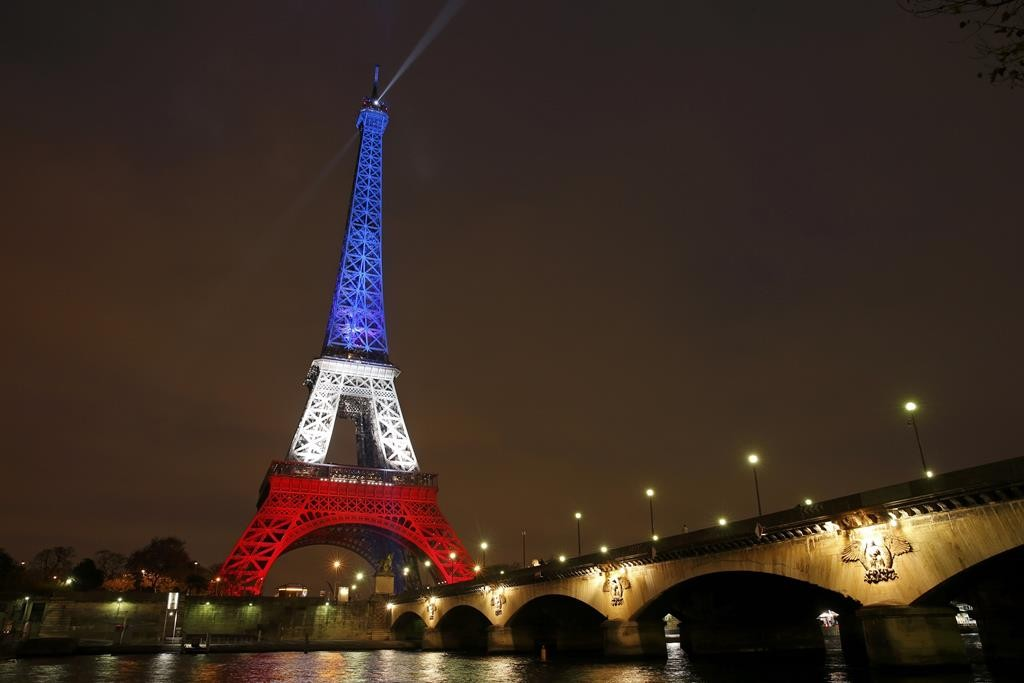 The Eiffel Tower is lit with the blue, white and red colors of the French flag in Paris, France, Monday, to pay tribute to the victims of a series of deadly attacks on Friday in the French capital.  (REUTERS/Benoit Tessier)
