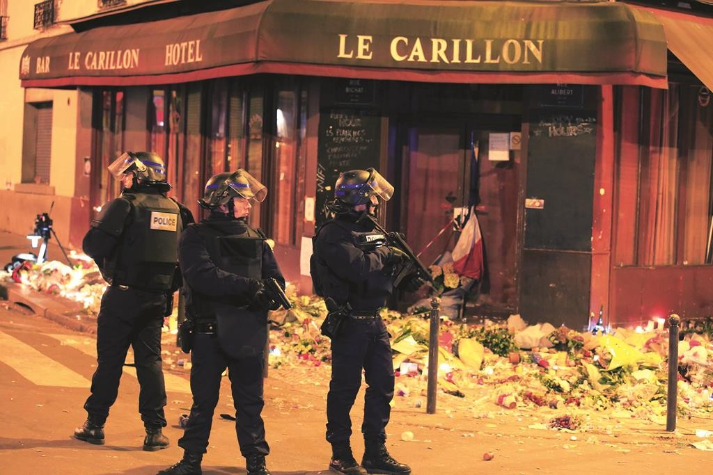 Police stand near La Carillon restaurant following a series of deadly attacks in Paris, Sunday. (REUTERS/Pascal Rossignol)