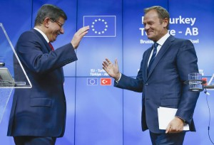 Turkish Prime Minister Ahmet Davutoglu (L) and European Council President Donald Tusk greet each other after a news conference following a EU-Turkey summit in Brussels, Belgium, on Sunday. (REUTERS/Yves Herman)