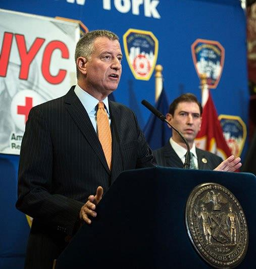 Mayor Bill de Blasio, flanked by Councilman Chaim Deutsch, announces on Monday that the city will install for free 100,000 smoke and carbon monoxide detectors. (Office of the Mayor)