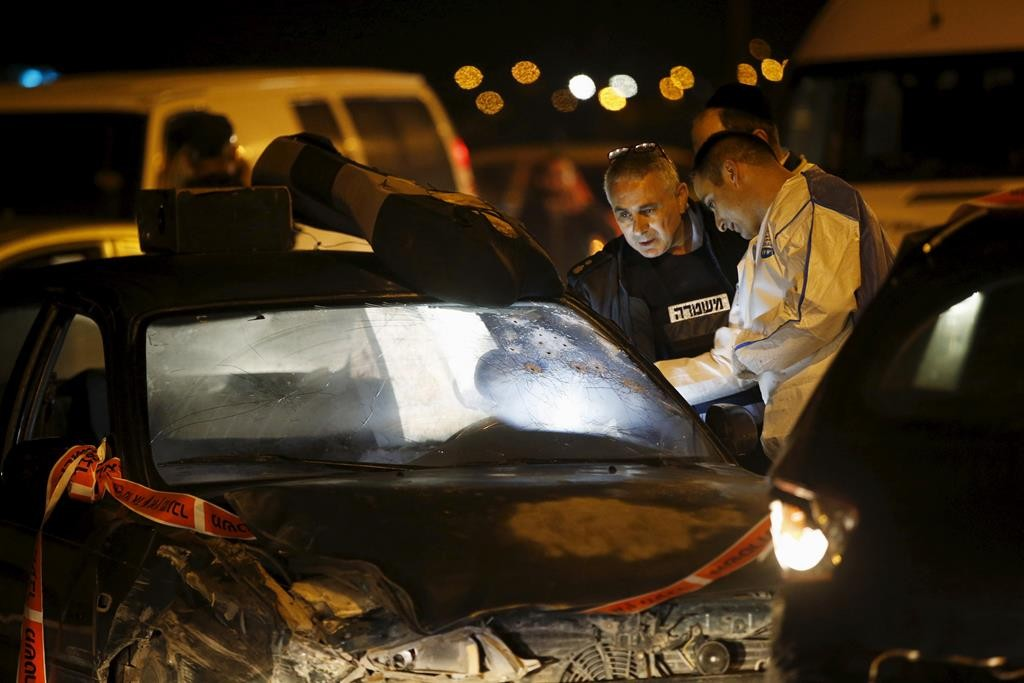 Israeli forensic policemen inspecting bullet holes on the windshield of a Palestinian terrorist's car at the scene of an attack near Alon Shvut in Gush Etzion, Thursday. (Reuters/Ronen Zvulun )