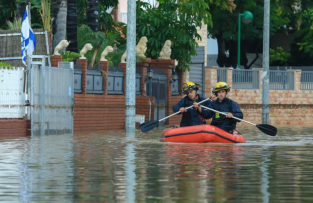Firefighters paddle across a flooded street after heavy rains in Ashkelon on Monday. (Edi Israel/Flash90)