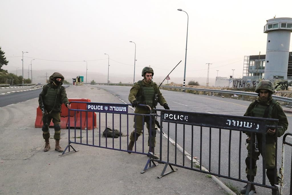 Israeli soldiers setting up a roadblock outside Halhul following a terror attack on Wednesday. (Gershon Elinson/Flash90)