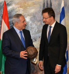 Hungarian Foreign Minister Peter Szijjarto (R) gives Israeli Prime Minister Binyamin Netanyahu a gift during their meeting at the Knesset, Monday. (Kobi Gideon / GPO)