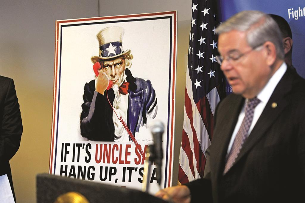"A sign reads ""If It's Uncle Sam, Hang Up, It's a Scam!"" as Sen. Robert Menendez speaks during a news conference Monday in Newark, N.J. (Danielle Parhizkaran/The Record via AP)"