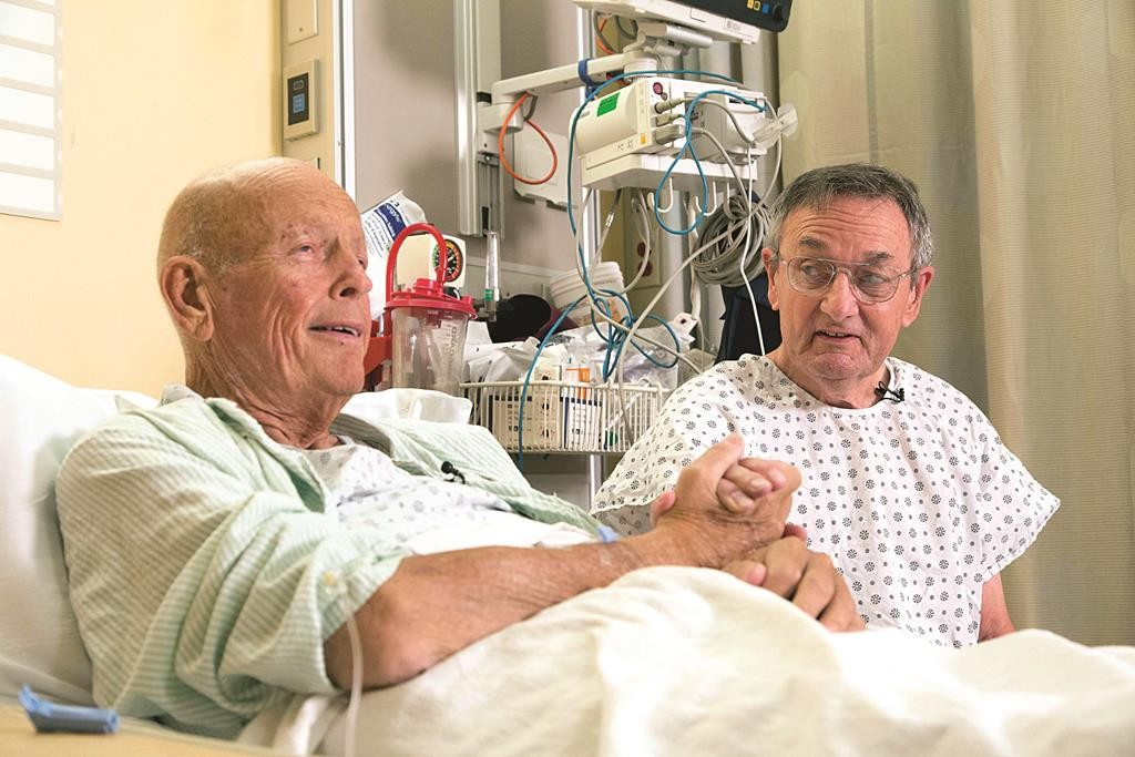 "Henry ""Bill"" Warner, left, and John Middaugh clasp hands prior to their surgeries Thursday at NewYork-Presbyterian/Weill Cornell Medical Center in New York. (AP Photo/Mark Lennihan)"